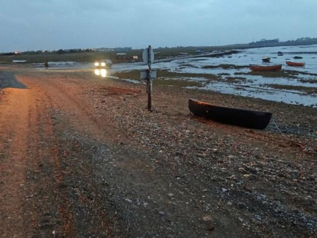 Shore at dawn with car headlamps